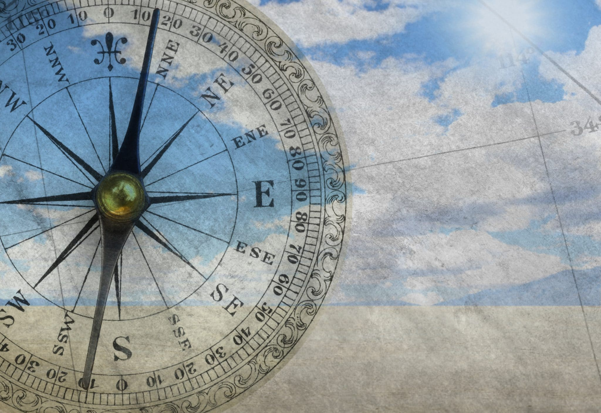 A multiple exposure of a vintage compass, an old map, and a scene from a remote desert conveying a sense of the unkown and adventure.
